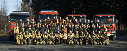 Ansatte i Brann oppstilt i lagformasjon foran brannbilene.