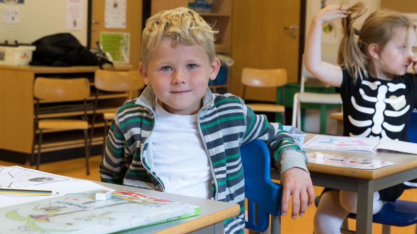 Gutt sitter ved skolepult.