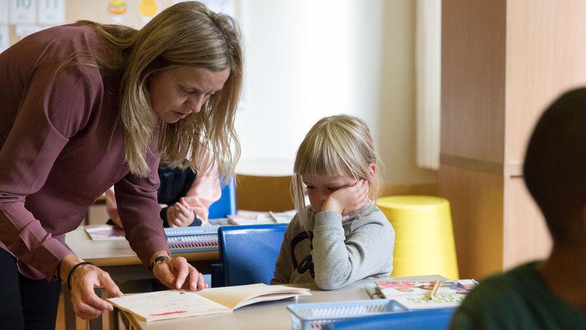 Jente får hjelp av lærer.
