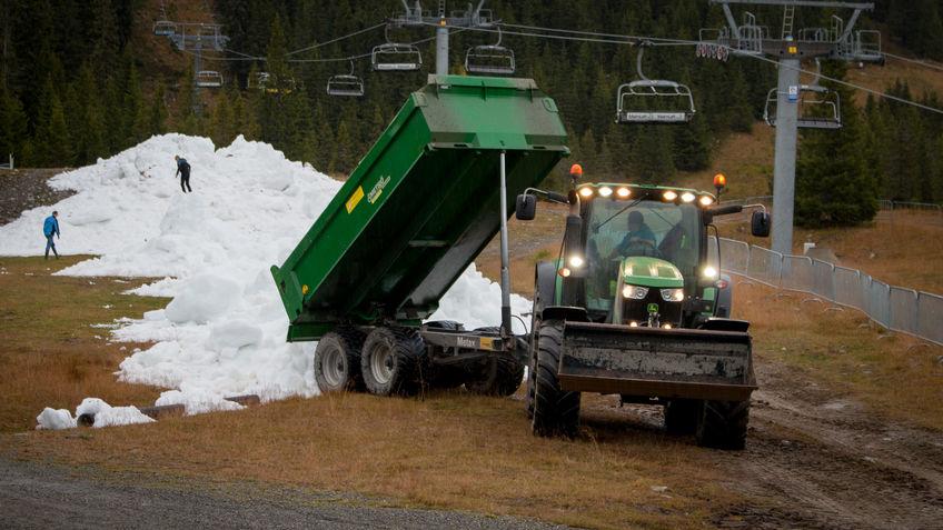 Snø lempes ut fra container