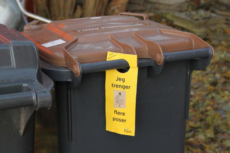 Gul lapp henger på avfallsdunken.