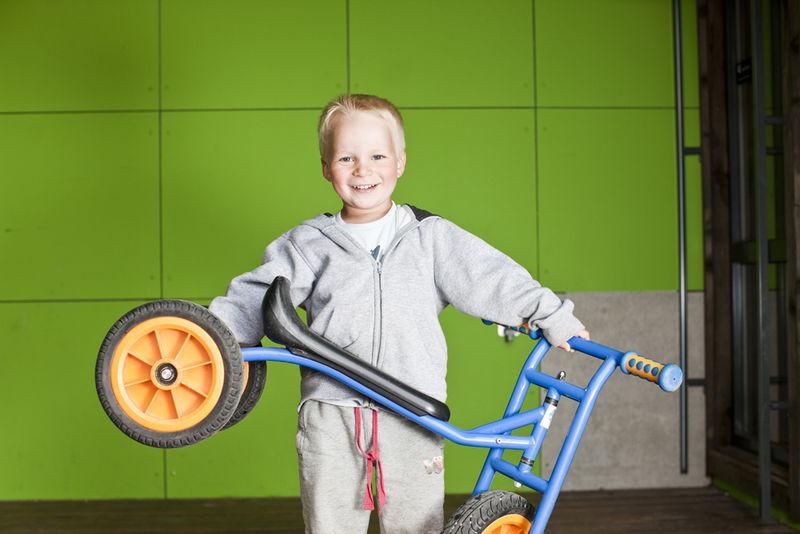 Barnehagegutt holder trehjulsykkel.