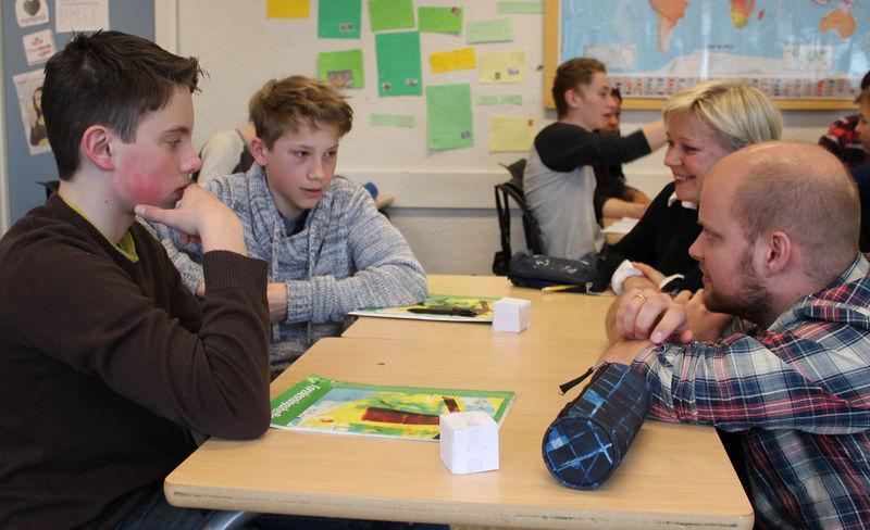 Fra venstre: Marius og Håkon i 9D diskuterer utregning av volum med mattelærer Lars Ole Godager Tveter. Kommunalsjef Anne Kari Thorsrud til høyre.
