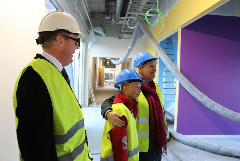 Rådmann, skoleleder og elevrådsleder inni den nye skolen.
