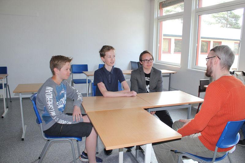 Skoleelever som prater med lærer