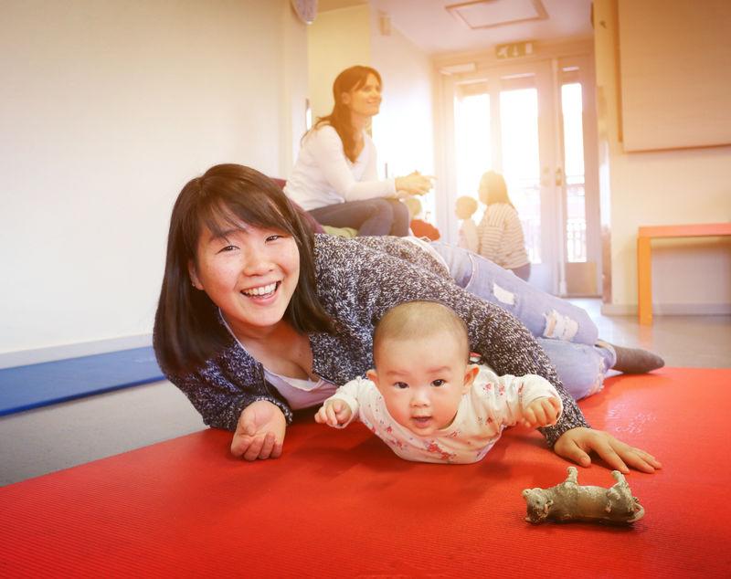 Mor og barn leker på gulvet