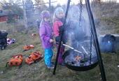 Barn griller mat på bålpanne