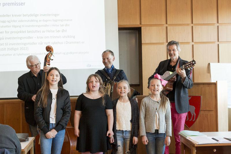 Barn og voksne som synger og spiller.