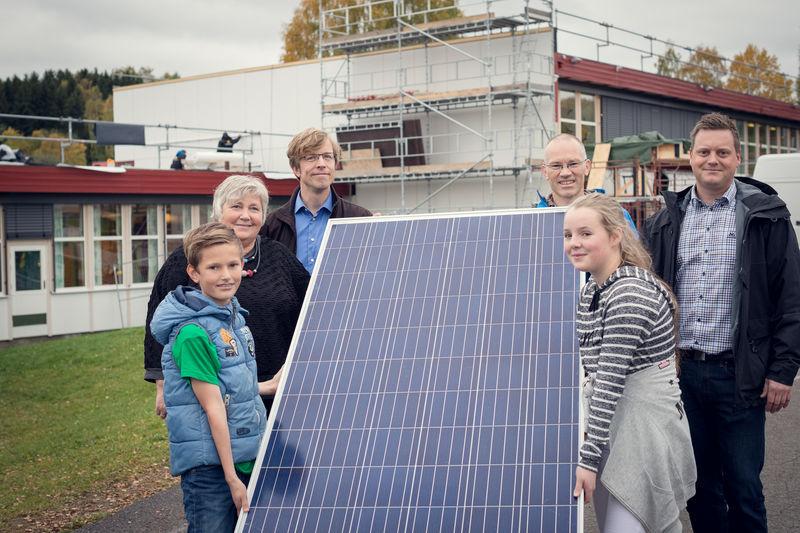 Voksne og barn som holder rundt et solcellepanel.