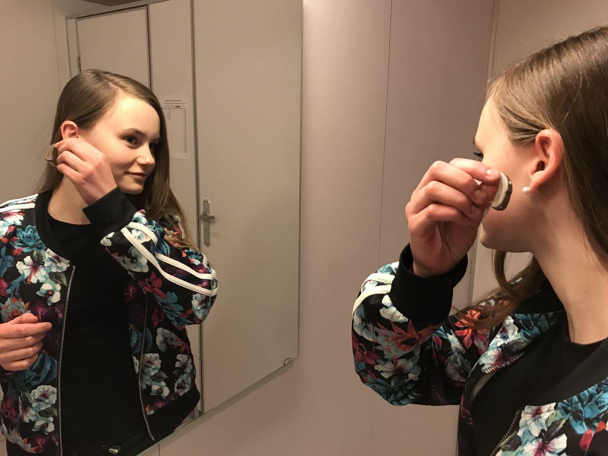 Linnea Fagermoen Apeland tar på seg høreapparatet