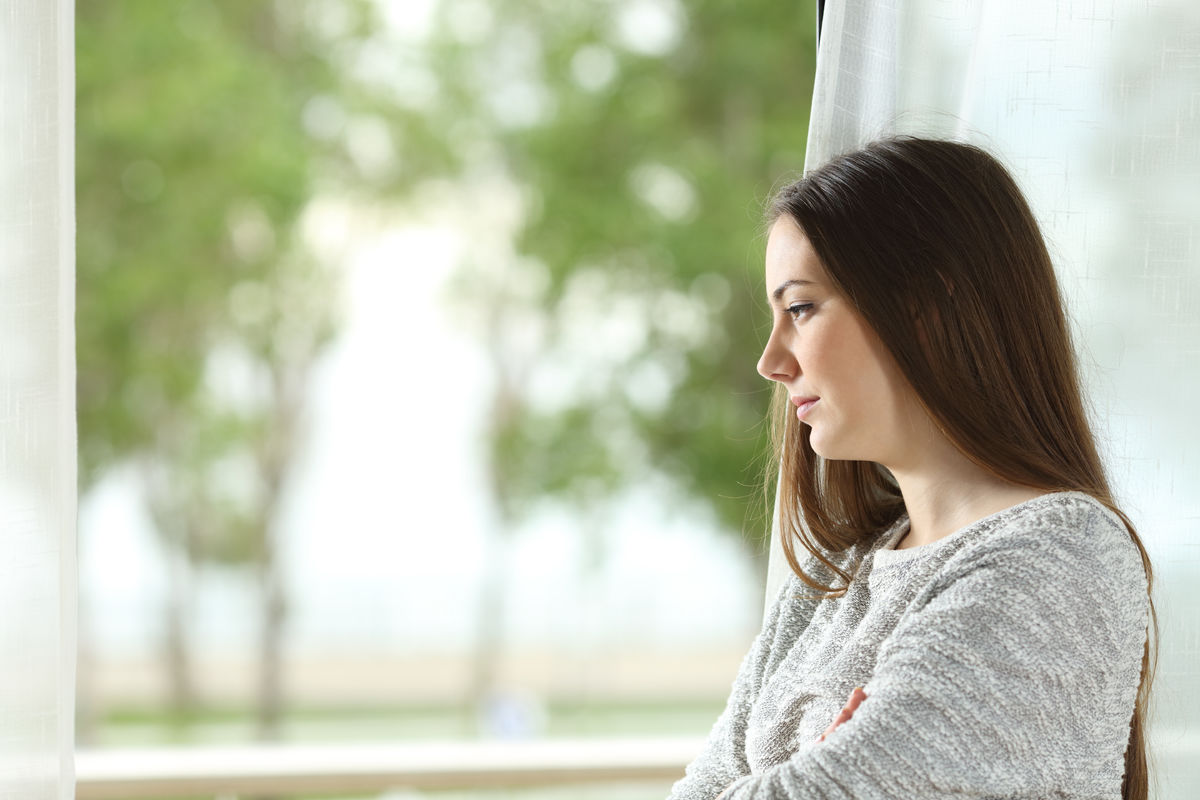 Longing woman looking through window at home