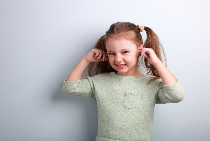 Cute fun kid girl coverd ears the fingers and gesturing that don