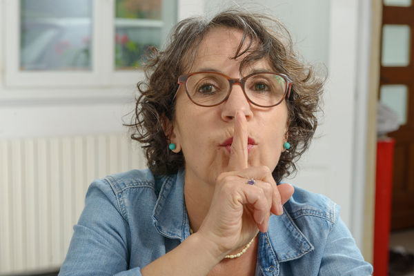 Portrait of mature woman with finger on lips