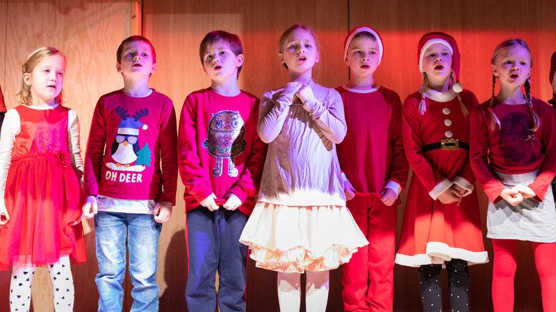 Barn med nisseluer som synger på en scene.