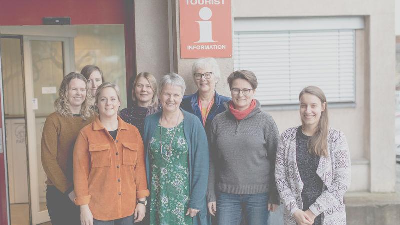Bilde av damer foran et Turistinformasjonsskilt