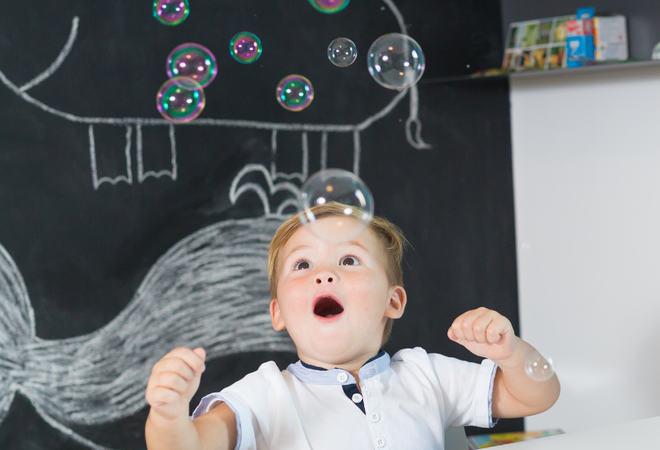 Portrait of cute toddler boy amazed by milky bubbles.
