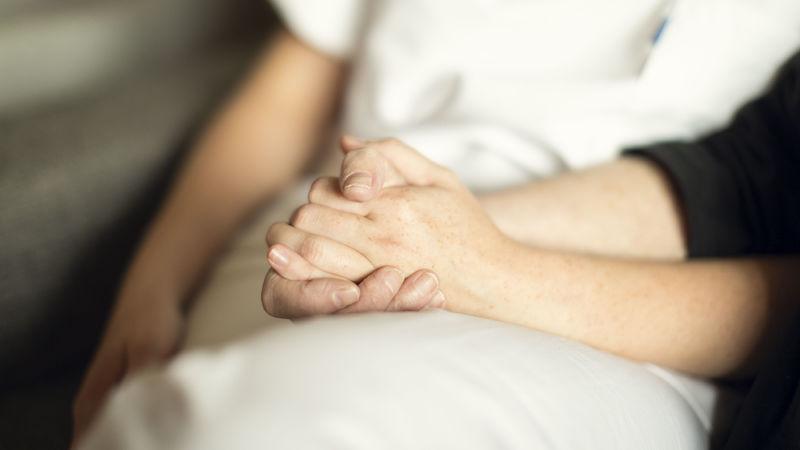 Foto av to som holder hender