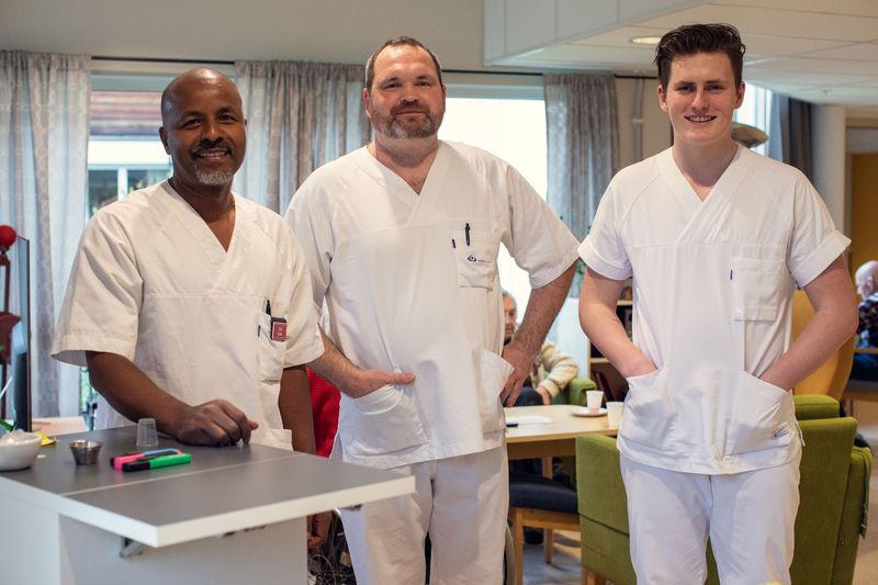 Tre menn i hvite helseuniformer