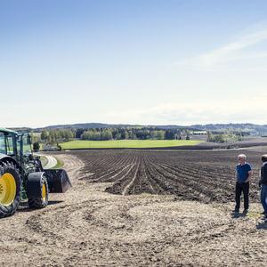 Foto av bønder, jorde og traktor