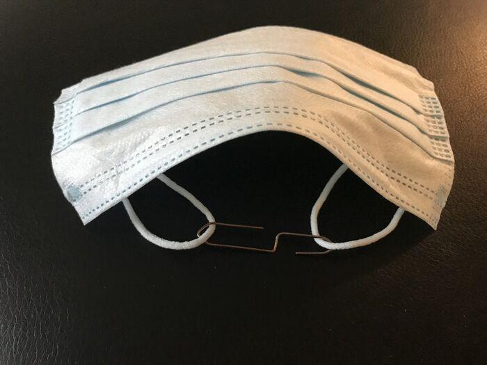 FORT GJORT. Slik skal bindersen festes til strikkene før du tar på deg munnbindet. Bruk større binders, dersom det blir for stramt.