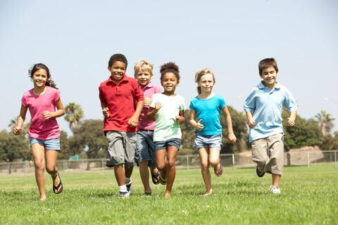 Barn som spring på ein plen