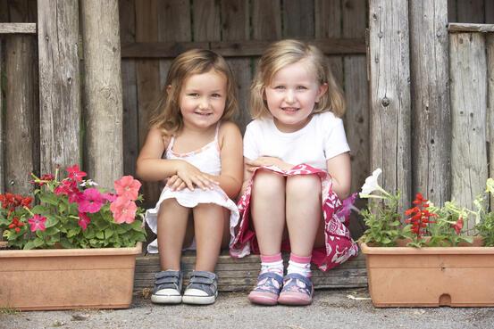 To jenter som sit ved sida av kvarandre