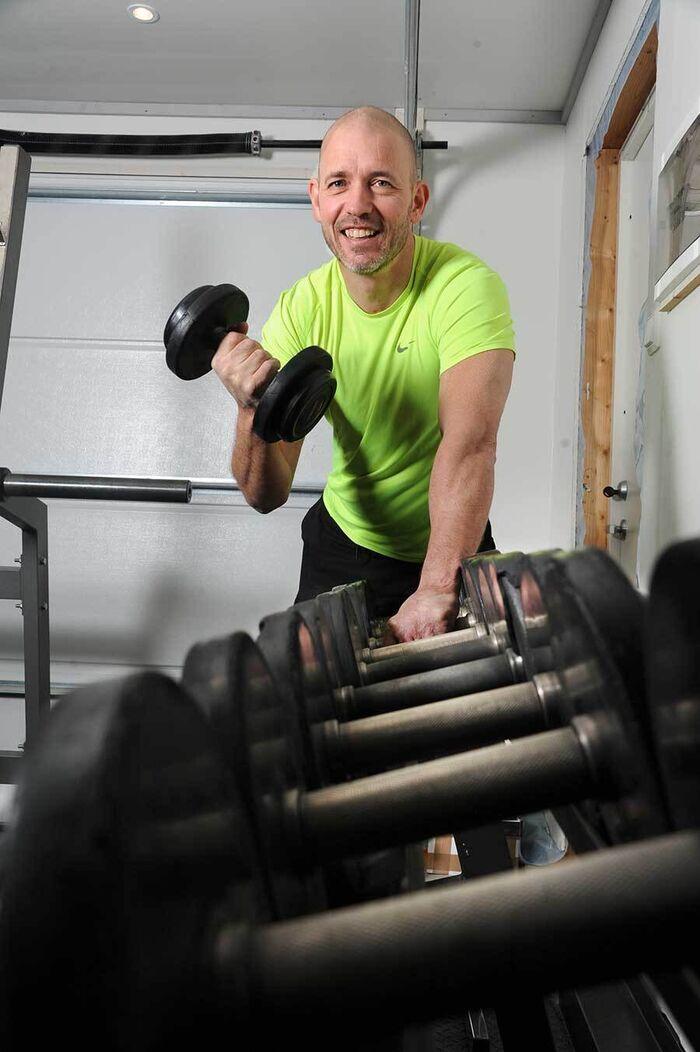 Kenneth trener med en vektmanual i et treningsrom.