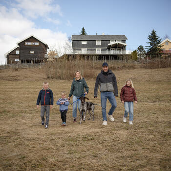 Tre barn og to voksne med hund på et jorde