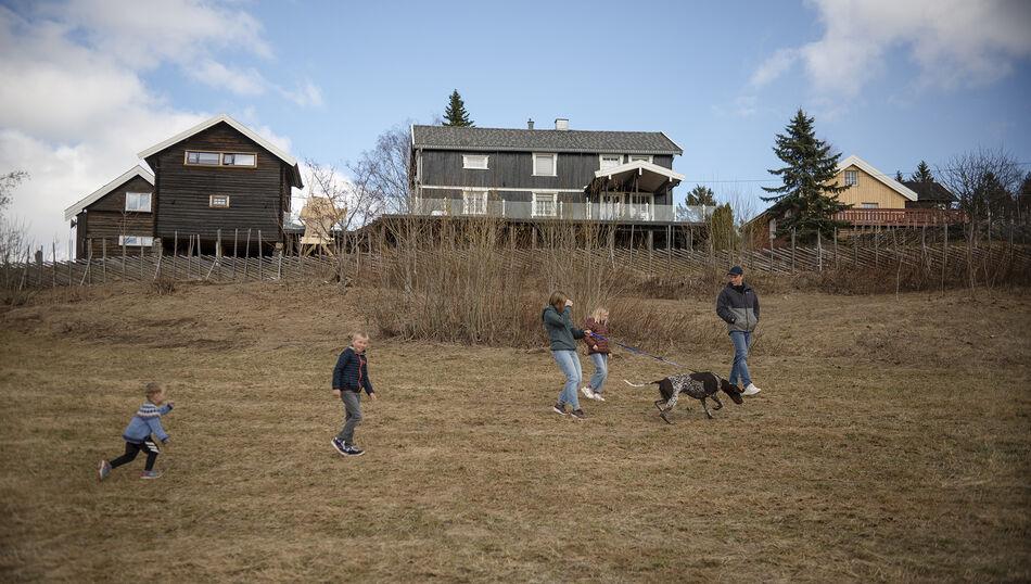 Tre barn og to voksne på et jorde