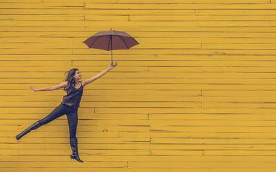 Dame_med_paraply_mot_gul_vegg