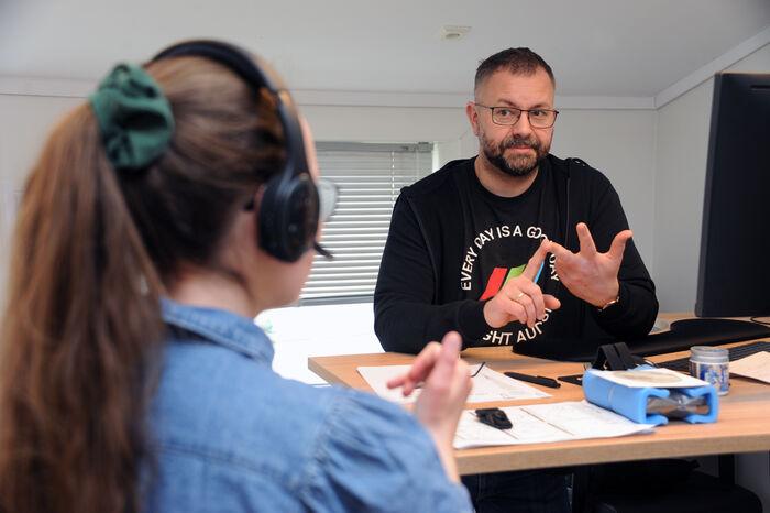TELEFONSAMTALE. Slik foregår alle telefonsamtaler på jobb. Via hodetelefoner oversetter tolk Malin Lundahl tale til tegn og motsatt til daglig leder Finn Arild Thordarson.