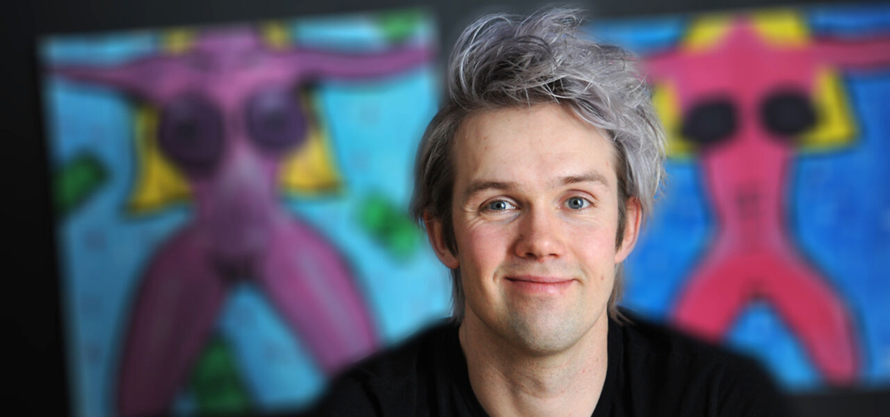 En smilende Nicholas Lund er fotografert foran en fargerik vegg.