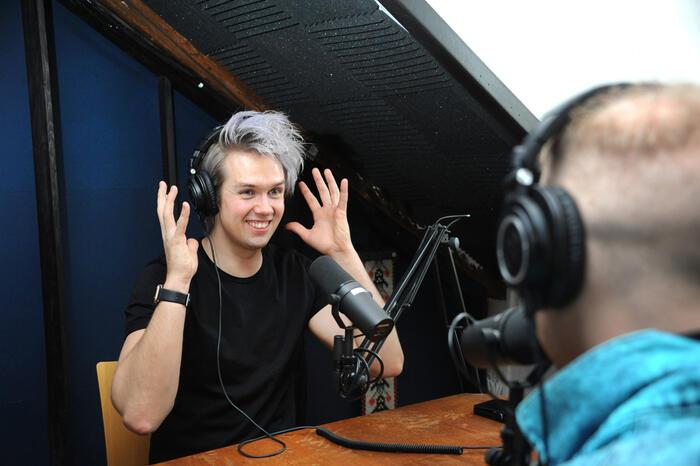 Nicholas Lund sitter med hodetelefoner i studio