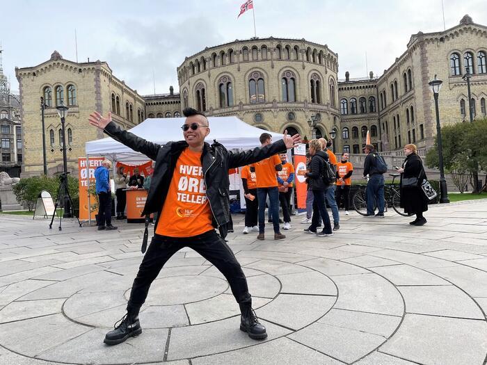 Høreapparatbruker Kitane Kinvares poserer foran HLF sin stand på Eidsvoll plass utenfor Stortinget.