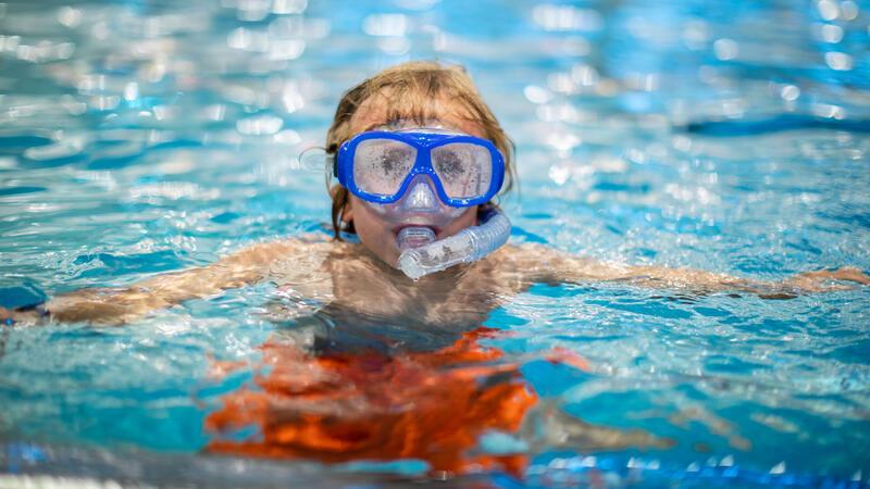 Barn som bader med snorkel og dykkemaske